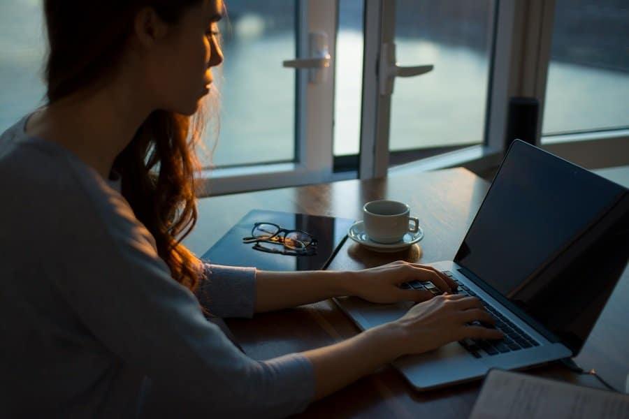 une personne écrit avec un ordinateur portable