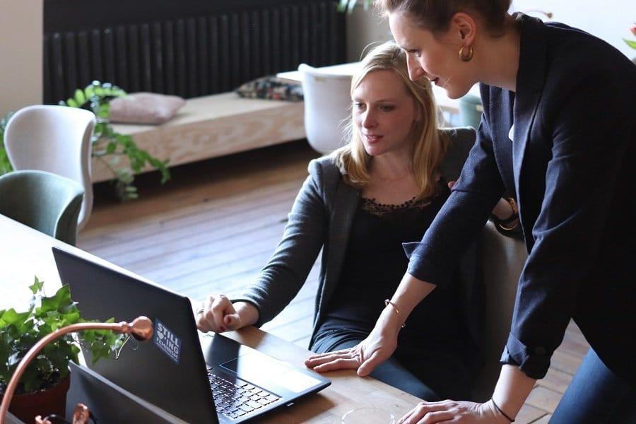 deux personnes discutent devant un ordinateur
