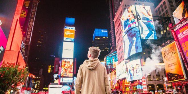 personne face à plusieurs bannières publicitaires sur Time Square, l'importance pour une entreprise de bien choisir ses supports de communication pour sortir du lot